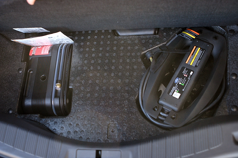 Hiding in the trunk: a flat kit and the car's power cord.